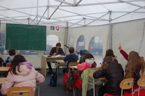 Učiteľ číta poznámky, deti si zapisujú. FOTO - Autorka